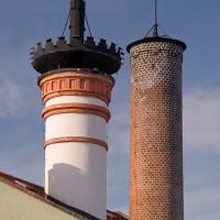 Původní komín má poměrně mohutnou zdobnou hlavici, novější má jen střídmou korunu.