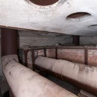 Vrchní část topeniště s potrubím výměníku tepla. Ze stropu vedou komínky o patro výše.