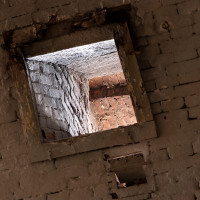 Okenní otvor v klenbě sklepení.
