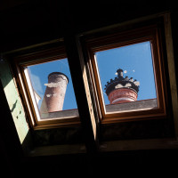 Zatím nepoužívanými střešními okny jsou vidět komíny hvozdu.