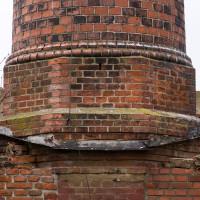 Příklop podstavce procházel střechou, za povšimnutí stojí tvarovkami zdobený přechod mezi maticí soklu a dříkem s kruhovým profilem.
